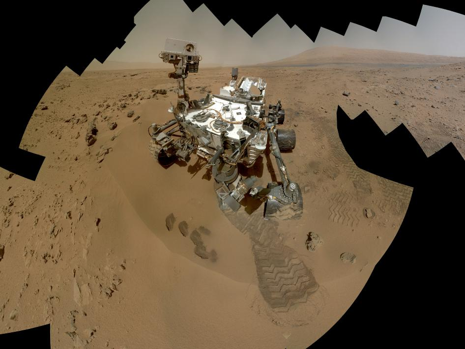 NASA's Curiosity rover scoops up rock samples on Mars. The planet's red color comes from rusty iron minerals in the sand and boulders on its surface. (Photo via NASA.gov)
