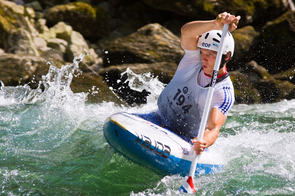 In this canoe slalom, a competitor fights rough water to execute quick turns along a natural river course. (Evronphoto/ Shutterstock)