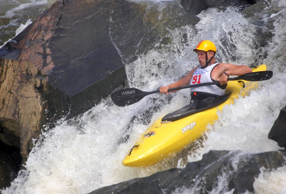 Another whitewater event is downriver racing. Run in wild rivers, these races can be as long as six miles through treacherous drops, waves, holes, and narrows. If kayakers take a tumble and hit a rock, padded helmets protect their heads. (2265524729 / Shutterstock.com)