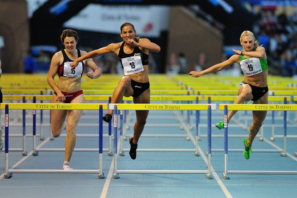 Olympian Lolo Jones (center) wins the 100-meter hurdles at an international competition. (Diego Barbieri/ Shutterstock)