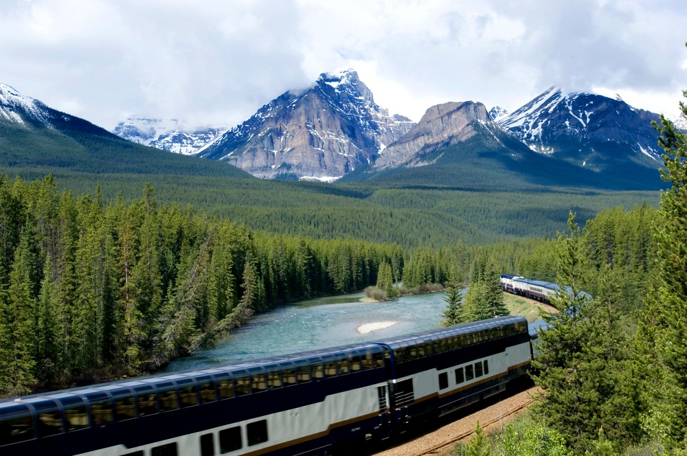 A tourist train rolls through the Canadian Rockies. The best seats on the double-decker passenger cars are on top, where there is a glass-domed roof. (Natalia Bratslavsky/ Shutterstock)
