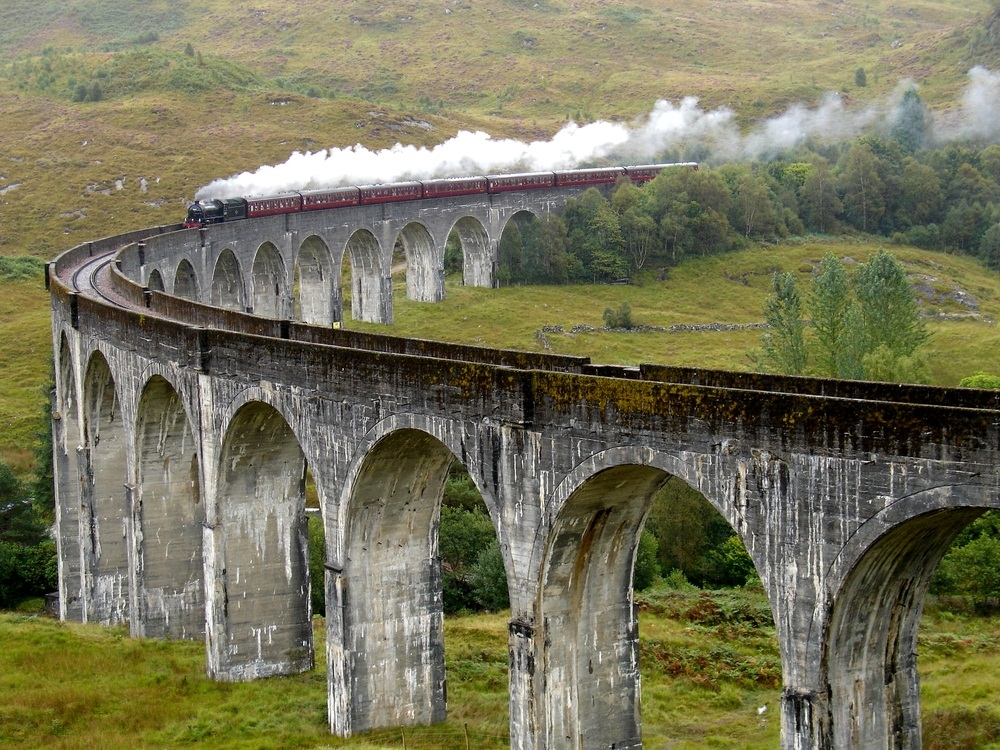 Here, a steam train called the Jacobite puffs through Scotland. The steam engine is on a locomotive at the front of the train, and the locomotive pulls the rest of the train down the tracks. The Jacobite appeared as the Hogwarts Express in the Harry Potter movies. (Serjio74/ Shutterstock)