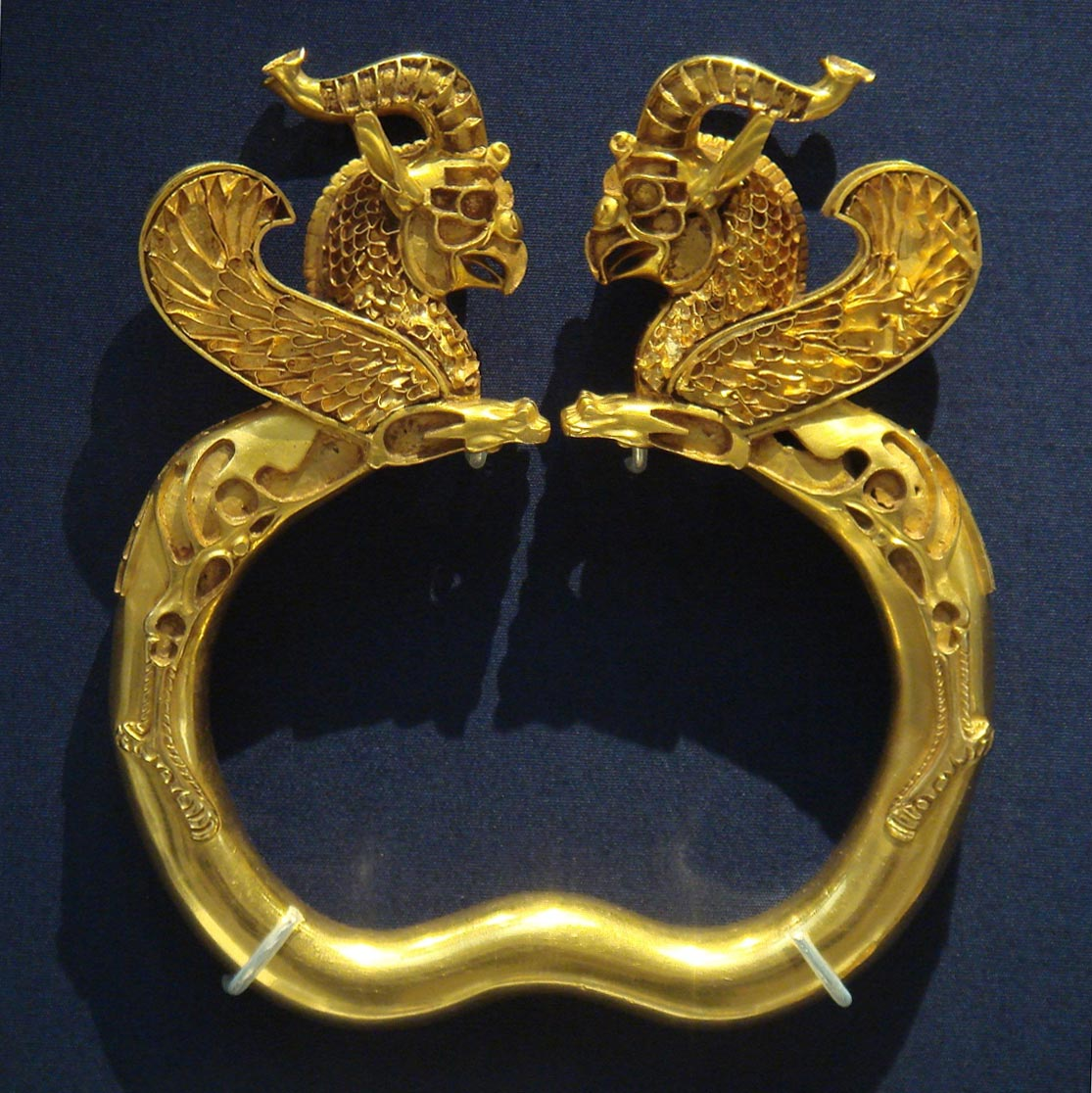 This gold bracelet was probably given as a gift of tribute to the royal court. It was one of about 170 gold and silver artifacts from the Archaemenid Empire found near the Oxus River in Tajikistan. The figures are two griffins, powerful mythical creatures, with the heads of eagles and bodies of lions, that the Archaemenids believed provided protection against evil.  (Photo via Wikipedia)