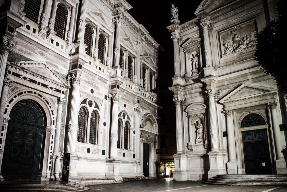 This church and scuola in Venice, Italy, are named for San Rocco, the patron saint of plague victims. The scuola on the left was built in 1485. The rounded arches, fluted columns, and triangular pediments are typical of Renaissance architecture.  (Odor Zsolt/ Shutterstock)