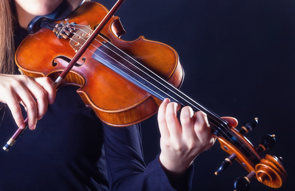Drawing a bow across a violin's strings causes them to vibrate. But the vibrations of the strings aren't strong enough to create very loud or musical sounds. The violin is built so the vibrations from the strings travel through the bridge (shown just above the bow) to the body of the violin. The body of the violin is a sound box and it vibrates, too, creating a rich, round sound and amplifying it.  (Artem Furman/ Shutterstock)
