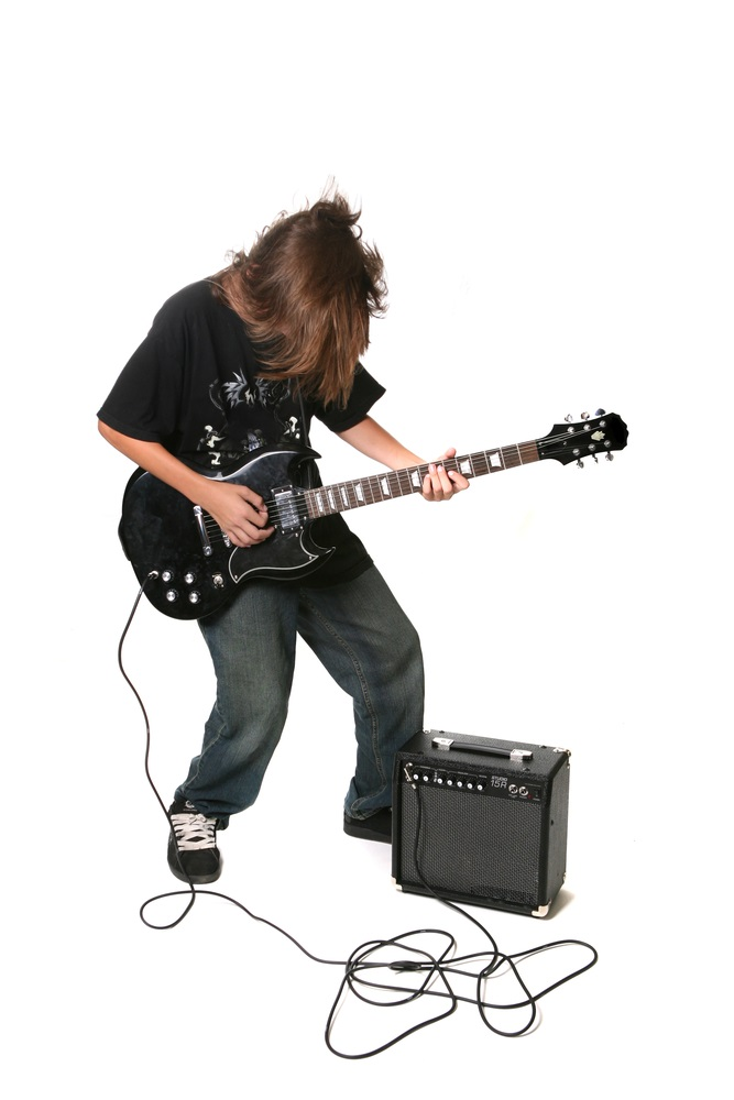 """Electric guitars don't sound like much when they're unplugged. Instead of sound boxes, electric guitars have """"pickups"""" which transform the strings' vibrations into electrical signals that can be played and amplified through a speaker. (tobkatrina/ Shutterstock)"""