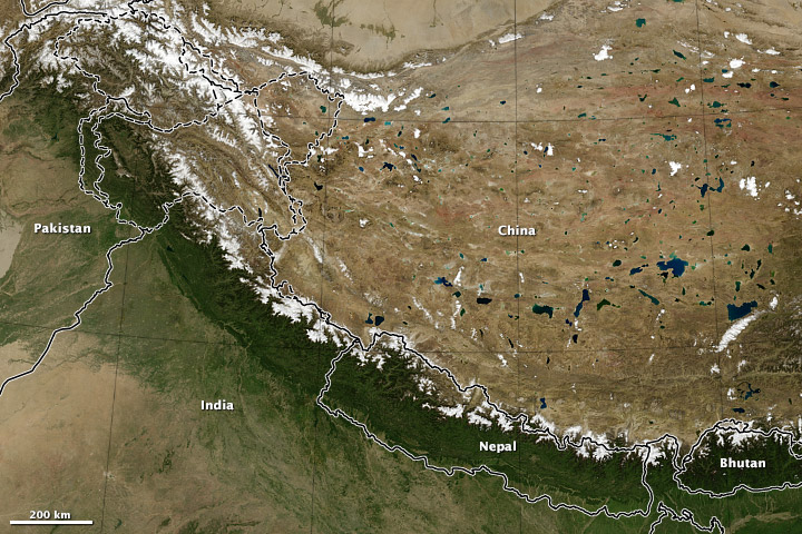 This satellite photo shows the wet, green southern slopes of the Himalayas and how the mountains block moisture from reaching the Tibetan plateau to the north.(Robert Simmon / NASA Earth Observatory)