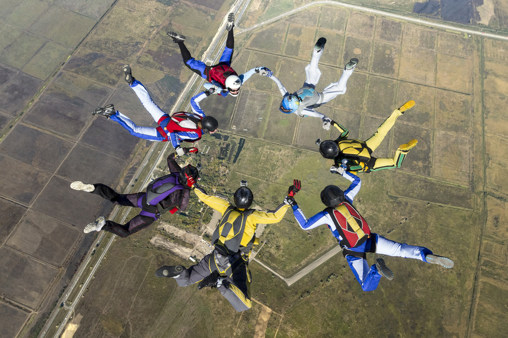 """These skydivers are in """"free fall."""" After jumping out of a plane from two-and-a-half miles up, they are being pulled back to Earth by the force of gravity. Before opening their parachutes, the only thing slowing their fall is """"air resistance."""" These sky divers will never fall faster than about 120 mph. But if one of them went into a """"diving"""" position and reduced air resistance, that skydiver could reach a top speed of about 200 mph. When you are in free fall, you feel weightless. (Shutterstock / Germanskydiver)"""